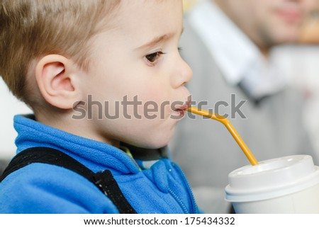 Happy kid with drinking straw boy on floor in living room at home - stock photo