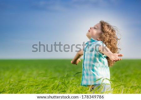 Happy kid with raised arms in green spring field against blue sky. Freedom and happiness concept - stock photo