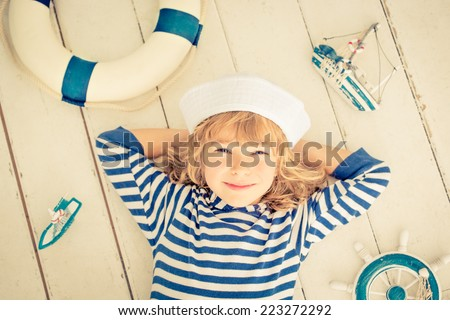 Happy kid with toy sailing boat. Child playing at home. Travel and adventure concept - stock photo