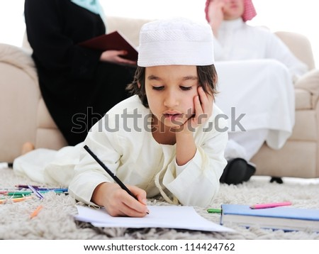 Happy kid working on homework at home with his family - stock photo