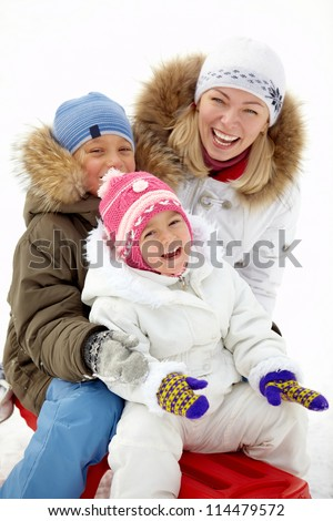 Happy kids and their mother sitting on sledge in park and laughing - stock photo