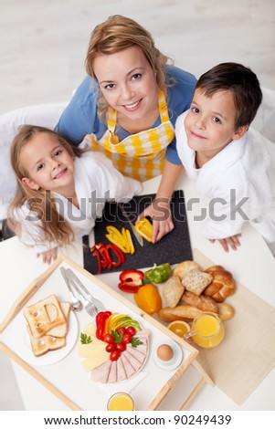 Happy kids and woman preparing healthy breakfast together - top view - stock photo