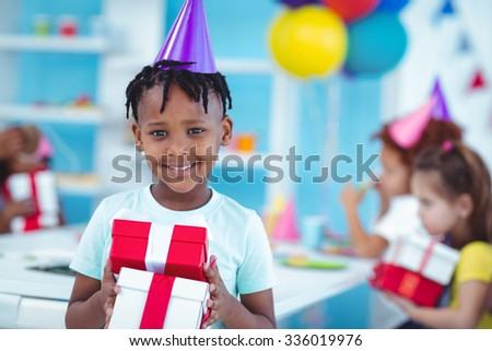 Happy kids at a birthday party about to open presents - stock photo