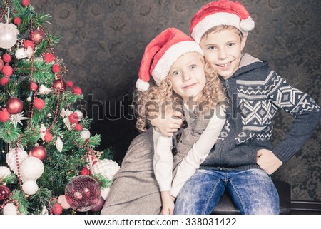 Happy kids at Christmas holiday near decorated Christmas tree. New Year. Concept of family celebration - stock photo