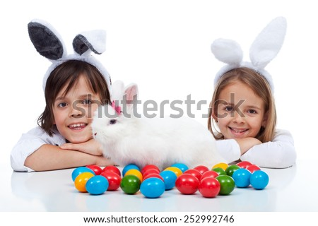 Happy kids at easter time - wearing bunny ears and guarding their white rabbit and colorful eggs - stock photo