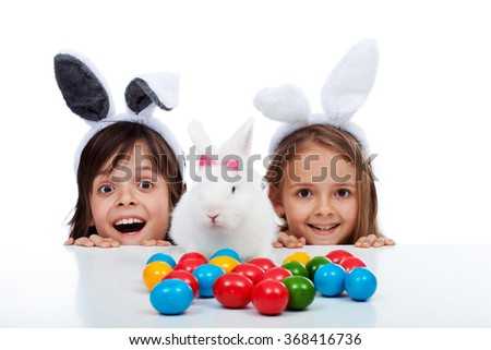 Happy kids at easter time with their white rabbit and colorful dyed eggs - focus on children - stock photo