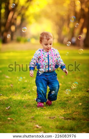 Happy kids blow bubbles outdoors