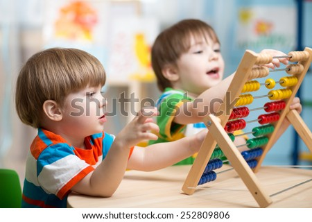 happy kids boys playing with abacus toy indoors - stock photo