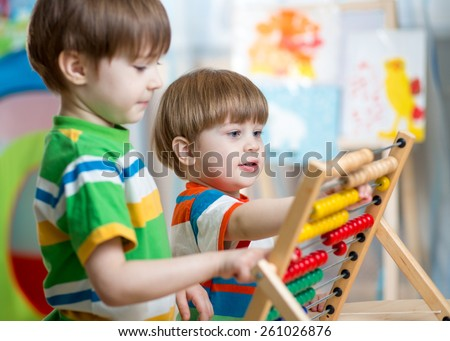 happy kids brothers play with abacus toy at children room - stock photo