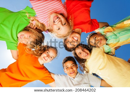 Happy kids close in circle on sky background - stock photo