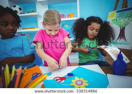 Happy kids doing arts and crafts together at their desk - stock photo