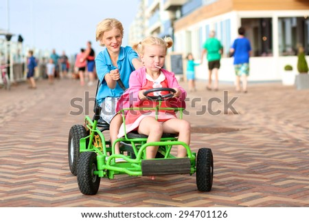 Happy kids enjoying active holidays on the beach. Sportive boy riding pedal car together with his cute toddler sister along the promenade on a summer day at sunset.