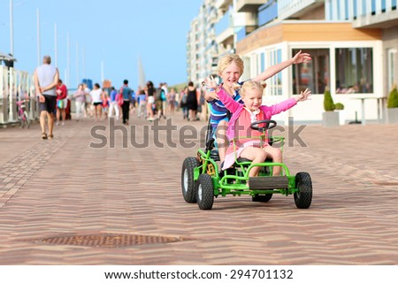Happy kids enjoying active holidays on the beach. Sportive boy riding pedal car together with his cute toddler sister along the promenade on a summer day at sunset.  - stock photo