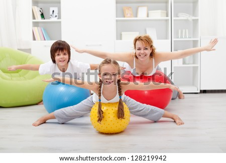 Happy kids exercising with their mother using large rubber balls - stock photo