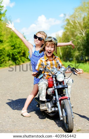 Happy kids go on a journey on a motorcycle on a bright sunny day. Adventure. Friendship. Summer holidays.  - stock photo
