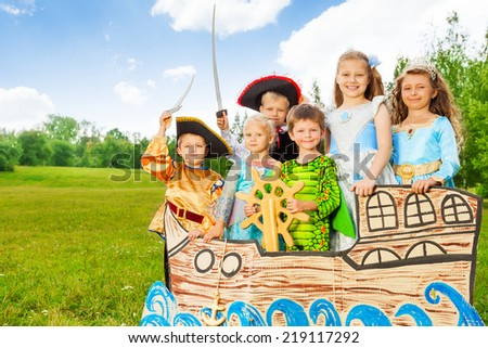 Happy kids in different costumes stand on ship - stock photo