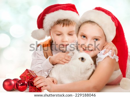Happy kids in New Year hat with white rabbit