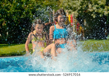 Happy kids in swimming pool have fun and splash in water, children on family vacation
