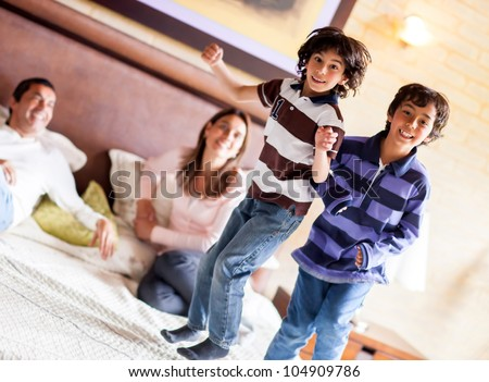 Happy kids jumping on the parents bed and having fun - stock photo