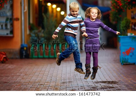 happy kids jumping under the rain - stock photo