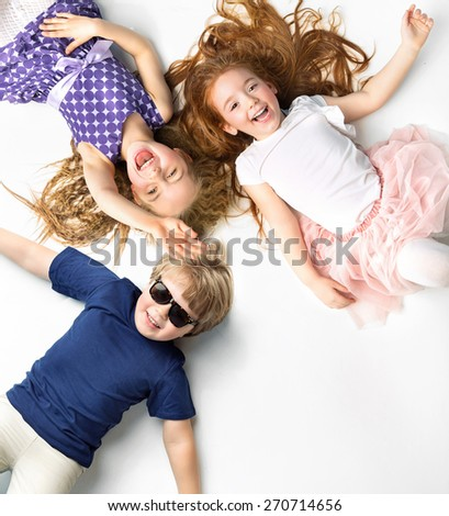 Happy kids lying on white background - stock photo