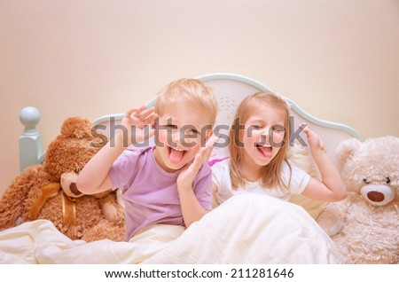Happy kids make faces, cute brother and sister make grimace, having fun at home, lovely family, active childhood concept - stock photo