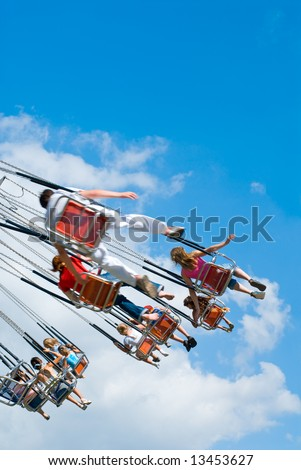 Happy kids on swinging carousel at blue cloudy sky - stock photo
