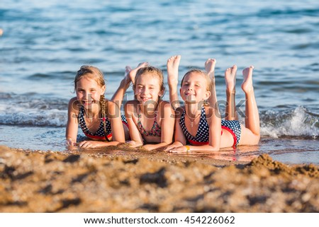 Happy kids on the beach having fun. Summer holiday concept - stock photo