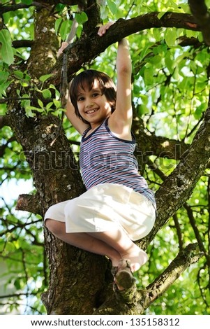 Happy kids outdoors in nature having good time climbing on the tree - stock photo
