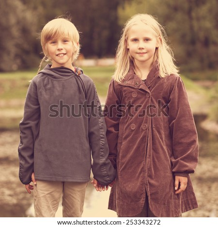 Happy kids outdoors, little boy and girl holding hands - stock photo