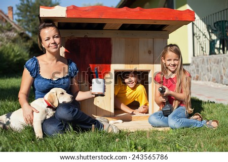 Happy kids painting the doghouse to shelter their new labrador puppy - stock photo
