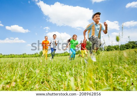 Happy kids playing and running in the field - stock photo
