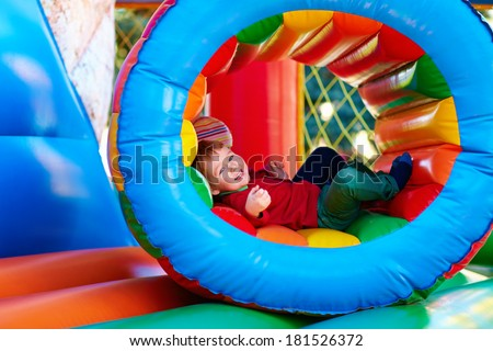 happy kids playing on an inflatable attraction playground - stock photo