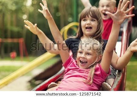 Happy kids playing on slide - stock photo