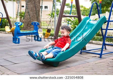 Happy kids playing on slide. Lovely school aged asian child on the chute