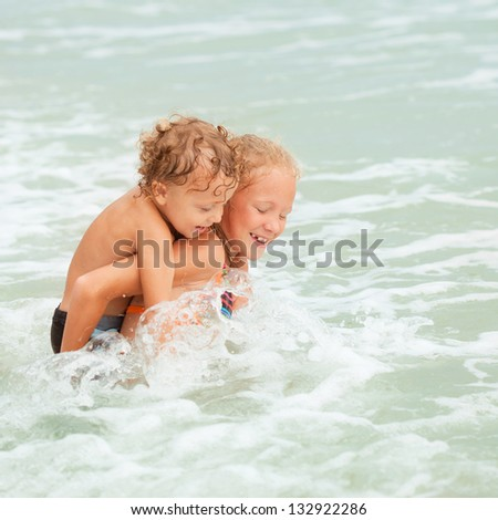 happy kids playing on the beach - stock photo