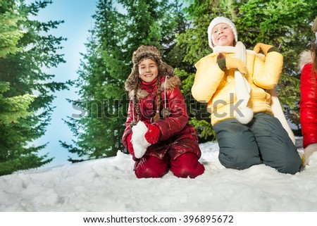 Happy kids playing snowball fight in a forest - stock photo