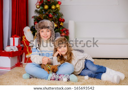Happy kids playing with dog chihuahua near the Christmas tree - stock photo