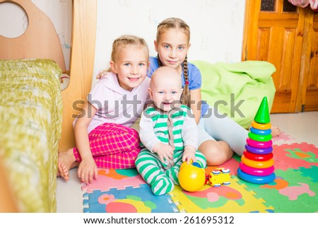 Happy kids playing with little brother in the room - stock photo