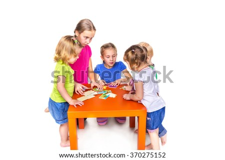 Happy kids playing with puzzles isolated on white. Team work, creativity concept.
