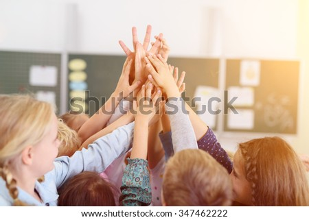 Happy Kids Putting their Hands Together in the Air Inside the Classroom. - stock photo