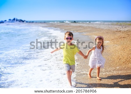 happy kids running along the seashore