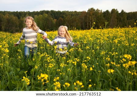 happy kids  sisters running around laughing  in the meadow in summer - stock photo