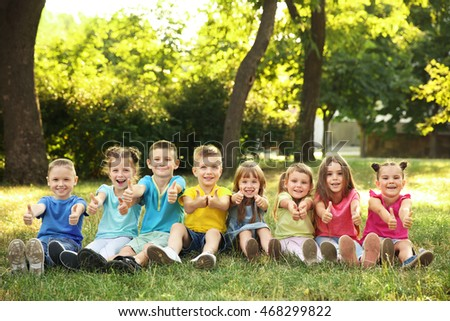Happy kids sitting on grass in park