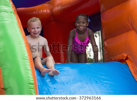 Happy kids sliding down an inflatable bounce house  - stock photo