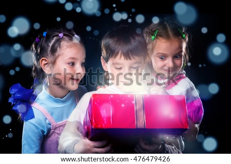 Happy kids surprised to open a present box magic light inside