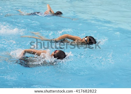 happy kids swim competition in swimming pool, healthy boy water sport front crawl race in summer - stock photo