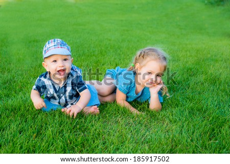 Happy kids together on green grass in spring park. Healthy lifestyles concept. - stock photo