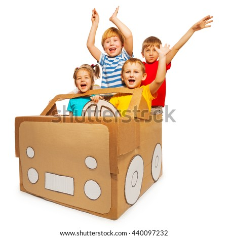 Happy kids waving hands sitting in cardboard car - stock photo