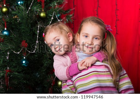 Happy kids with Christmas presents near Christmas tree